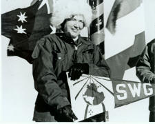 Jackie poses at the South Pole with Society of Woman Geographer's flag, in 1971.  Navy photo